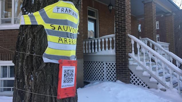 Un chandail jaune et blanc, accroché à un arbre, sur lequel il est écrit Tramway : sauvons les arbres