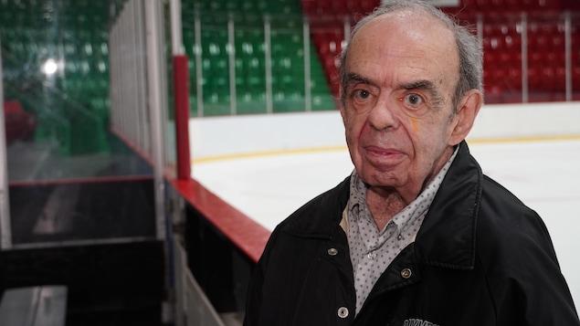 Un homme pose devant la glace d'une aréna.