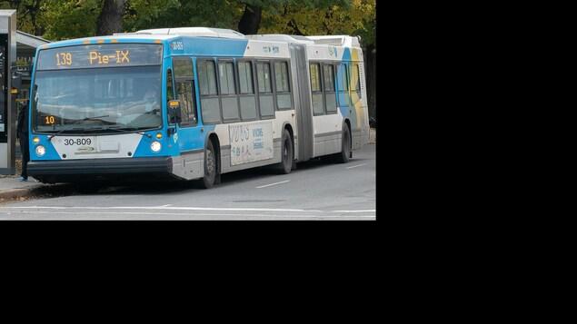 Un autobus accordéon de la STM à un arrêt.