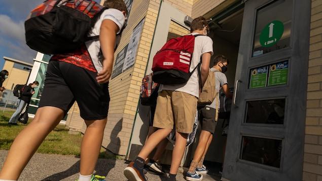 Des élèves portant le masque, entrent dans une école.