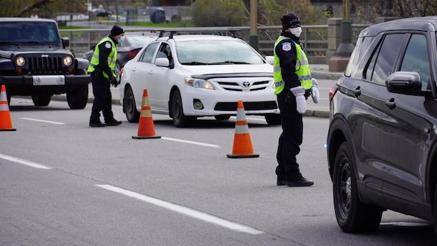 Des policiers s'adressent à des automobilistes dans une file de voitures.