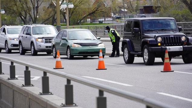 Un policier s'adresse à un automobiliste, dans une fil de voitures.