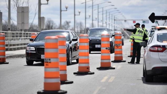 Un policier fait un signal à une voiture qui approche d'un contrôle routier.