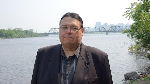 Portrait de l'homme placé devant la rivière des Outaouais et le pont Chef-William-Commanda.