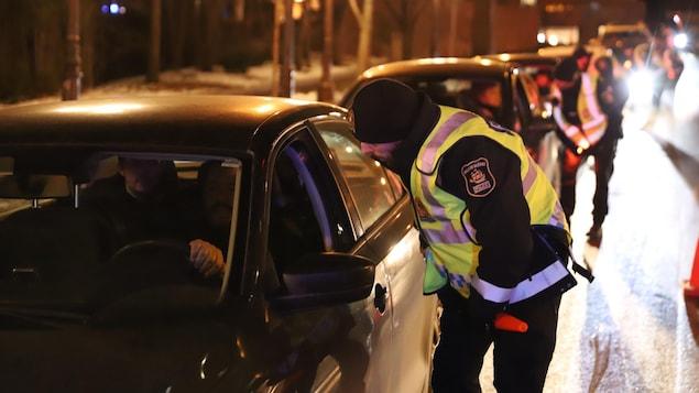 Une file des voitures arrêtées par des policiers dans la nuit.