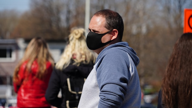 Un homme porte un masque de protection.