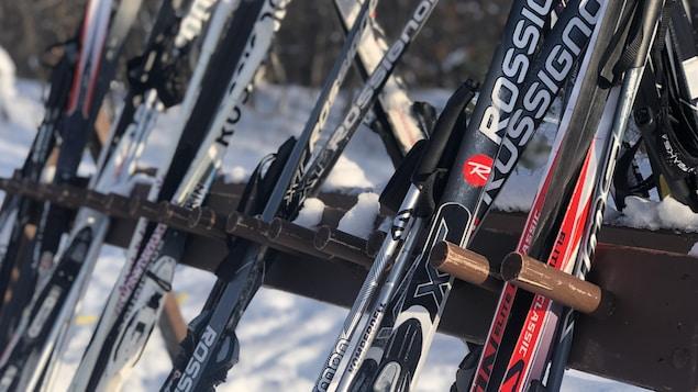De l'équipement de ski de fond sur un support en bois à l'extérieur l'hiver.