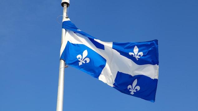 Un drapeau du Québec flotte au vent.