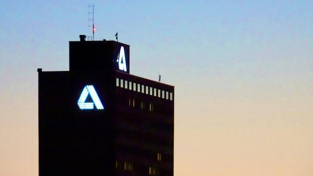 La silhouette de la tour et le « A » allumé sur la façade, à la tombée du jour.