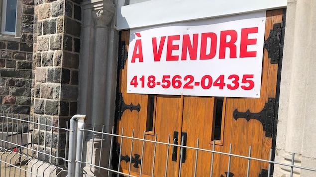 """Une grosse affiche """"À Vendre"""" avec un numéro de téléphone, est collée sur la porte de l'église, qui est entourée d'une clôture."""