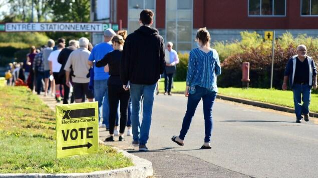 Des gens font la file pour aller voter.