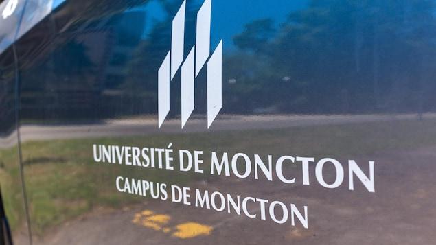 Le logo de l'Université de Moncton, campus de Moncton, imprimé sur le côté d'une voiture.
