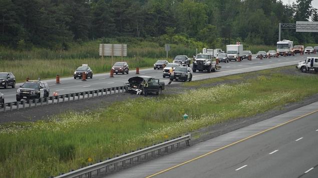 Un accident sur une autoroute, avec de la circulation autour et des policiers au travail.