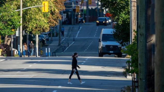 Une piétonne avec un masque traverse une rue.