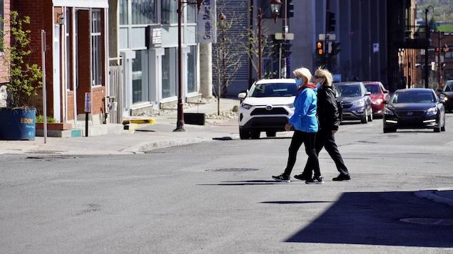 Des piétons portant un masque traversent la rue.