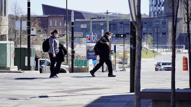 Des piétons portant le masque marchent dans une rue.
