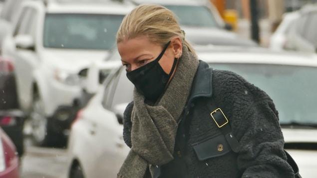 Une femme marche avec son masque.