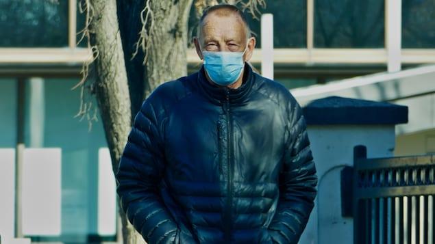 Un homme marche dans la rue en portant un masque.