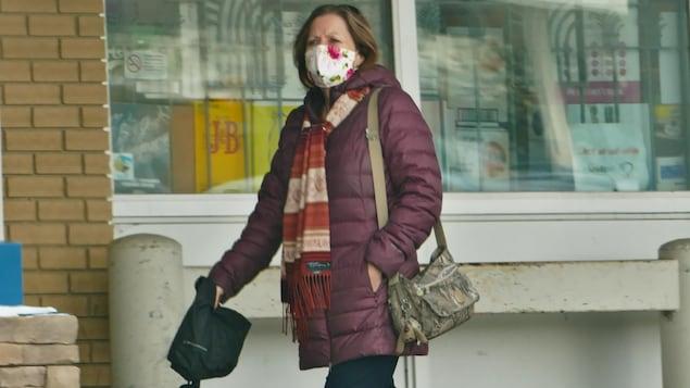 Une femme porte un masque à l'extérieur pendant la pandémie de la COVID-19 à Regina en hiver.