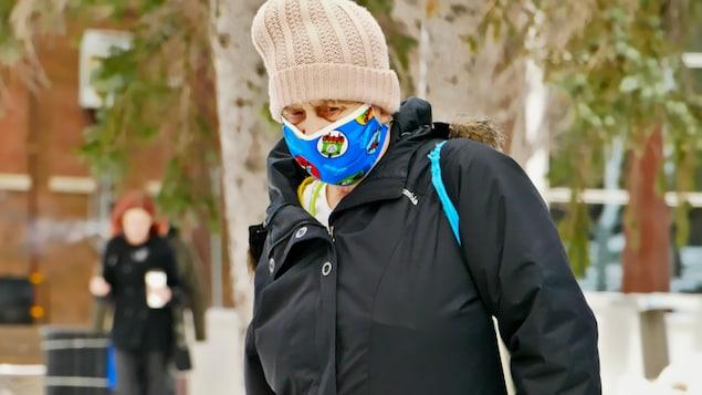 Une femme vêtue d'un manteau d'hiver et d'une tuque portant un masque.