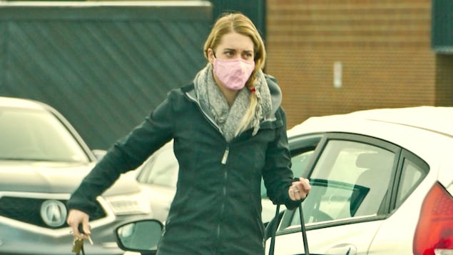 Une femme en manteau d'hiver et portant un masque traverse un stationnement.
