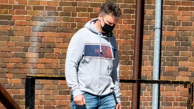 Un homme porte un masque en marchant dans la rue.