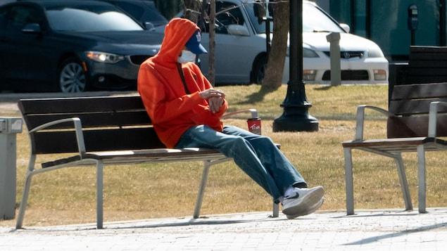Un garçon, vêtu d'un chandail orange, s'apprête à boire un café sur un banc de parc.