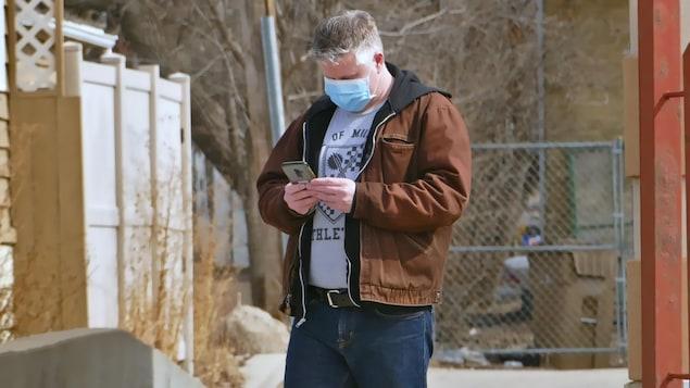 Un homme portant un masque regarde son téléphone.