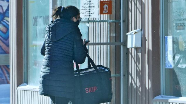 Une personne porte un sac de livraison d'un restaurant.