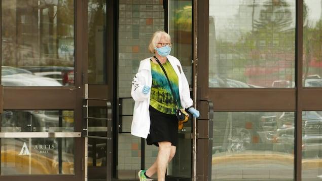 Une femme marche dans les rues de Regina en portant un masque.