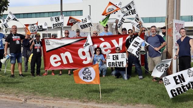 Des travailleurs brandissent des pancartes indiquant «En grève».