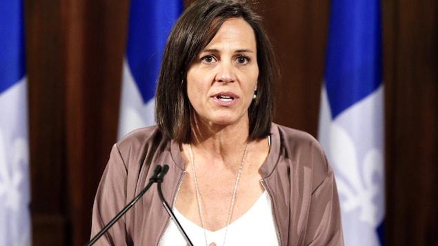 Une femme parle dans un micro pendant une conférence de presse.