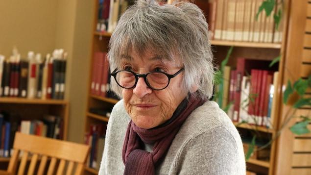 Une femme explique des nuances de la langue innue devant des livres anciens en langue innue.