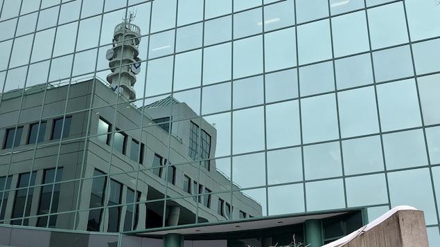 L'hôtel de ville se reflète sur la façade vitrée d'un bâtiment voisin.
