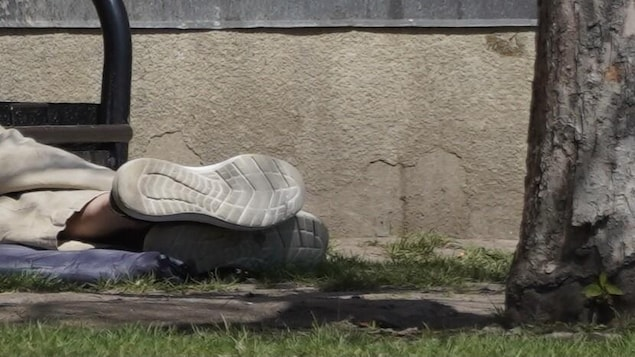 Les pieds d'une personne allongée par terre, dehors.