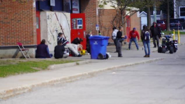 Des personnes dehors devant un bâtiment, dont certaines assises.