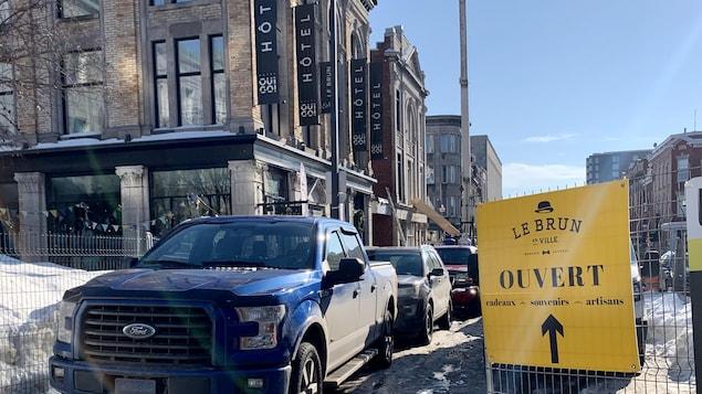 L'hôtel oui go et des clôtures délimitant le chantier, avec une affiche indiquant où se trouve le magasin.