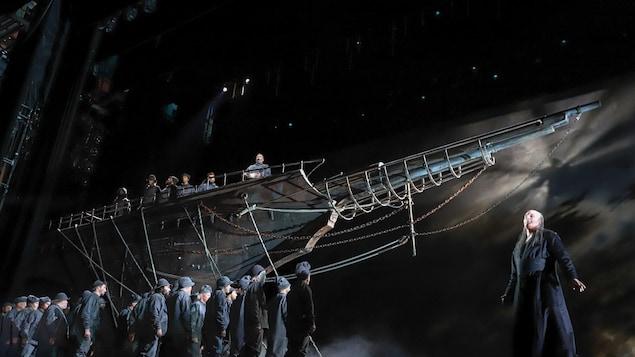 Un chanteur d'opéra chante sur scène. Derrière lui se trouve un bâteau et une vingtaine de marins.