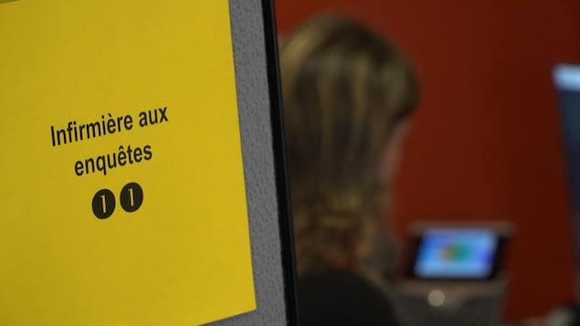 Gros plan sur une feuille de papier jaune sur laquelle sont écrits les mots « infirmière aux enquêtes ». La feuille est affichée sur une cloison délimitant un espace de travail. On aperçoit, à l'arrière-plan, une femme parlant au téléphone.