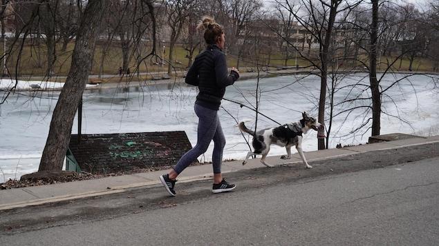 Une femme fait de la course à pied avec son chien.