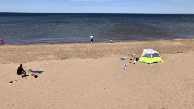 Quelques personnes sur la plage à plusieurs mètres de distance les unes des autres.