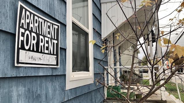 Une pancarte d'appartement à louer affichée sur une maison bleue.