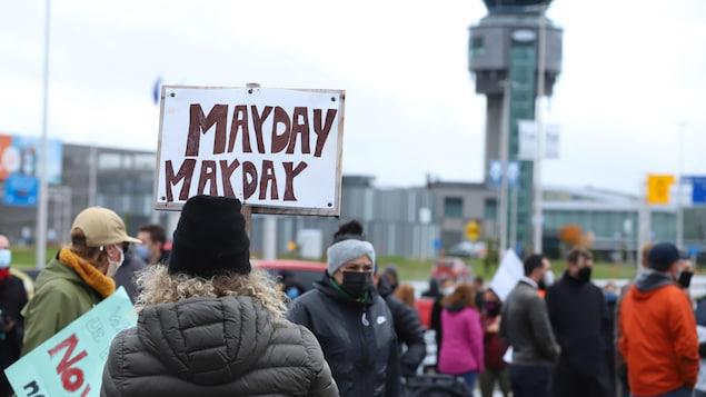 Des manifestants avec des pancartes sur le terrain de l'aéroport de Québec.