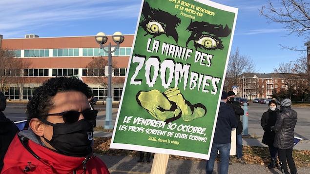Un homme manifeste avec une affiche en main.