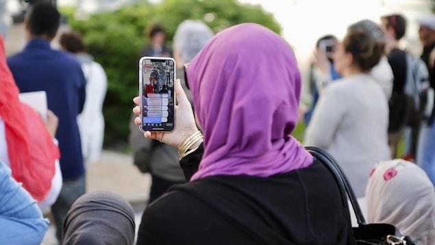 Une femme voilée de dos tient son téléphone dans une foule.