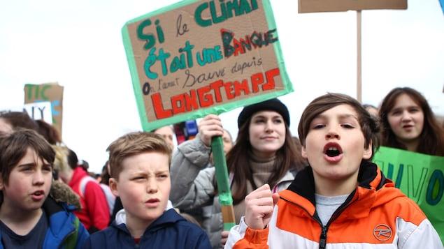 Des jeunes tiennent des pancartes à l'extérieur.