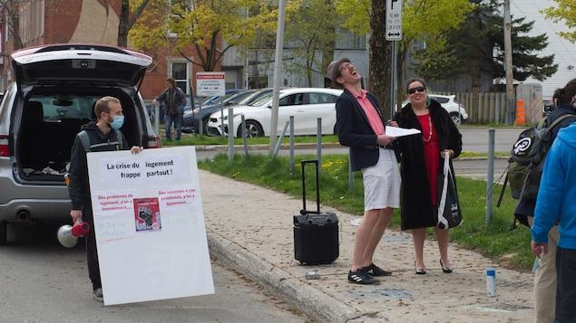Un manifestant tient une affiche et un porte-voix et deux autres sont déguisé en « riche ».