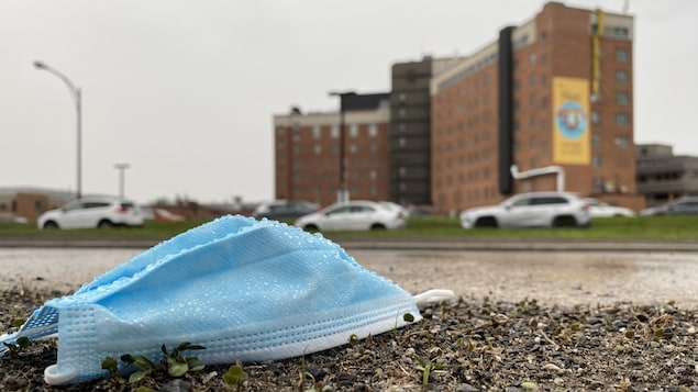Gros plan sur un masque au sol avec, en arrière plan, l'Hôpital de Hull.
