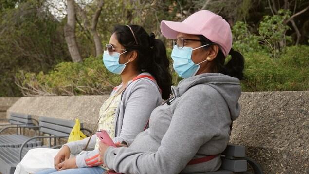 Deux femmes assissent sur un banc de parc portant un masque à Saskatoon en été. Plan serré.