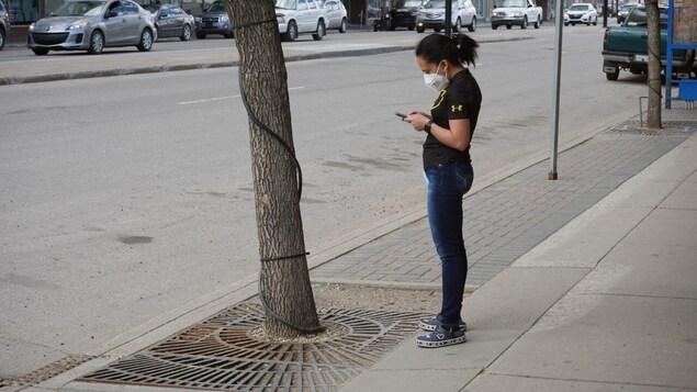 Une personne regarde son cellulaire dans la rue avec un masque au visage.